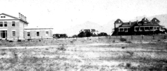 "Facing north toward the Santa Catalina Mountains, c. 1902. (left to right) The south end of South Hall, the roof of the two-story home of Professor Foucar, North Hall, and the School of Mines or Main Building, now called ""Old Main."""