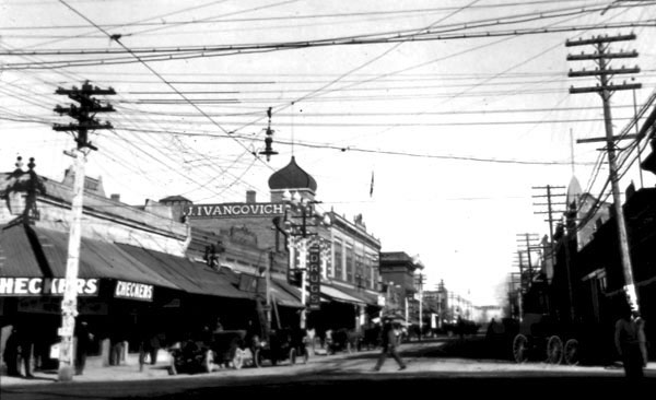 "The streetscape of Congress Street looking east. T. Ed. Litt Drug Store was located in the building with the sign ""Checkers."" Continuing along the north side of the street was Fred Fleishman Drugs, J. Ivancovich Grocery, the YWCA (probably upstairs), the Opera House, S. H. Kress, M. & B. Meyers and Bloom, and Kitts Dry Goods."