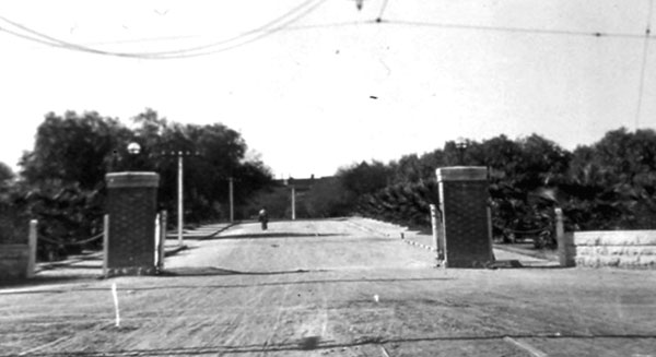 The Main Gate entrance to the University. In 1905, in anticipation of the electric trolley replacing the horse or mule drawn trolley, the barbed wire fence and wooden turnstile was replaced with brick pillars and a low, stone wall.