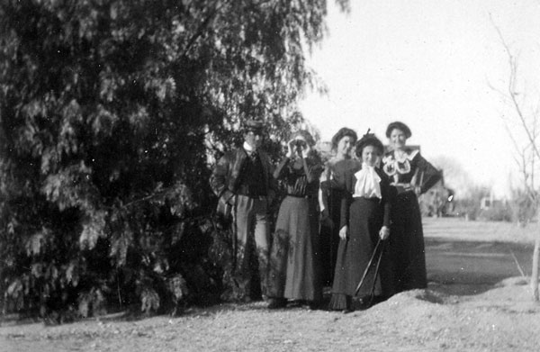 A man and four women pose for the camera