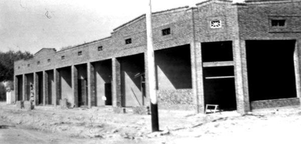 A view of the entrance to the corner drug store and complex while still in construction.