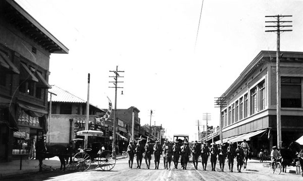 A military contingent marching east on Congress Street, c. 1914. Notice the troller tracks running down the middle of the streets with horse and buggies on either sides and bicyclists.