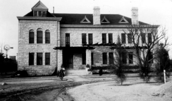 North Hall was the only stone building constructed on campus. A sleeping porch was added at the rear in 1911 and the heavy porch timbers in 1915. The windmill and water tank (left) are at the Marshall home.