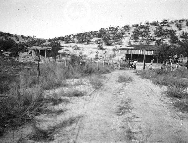 Perhaps a ranch in the area. A man, woman and dog stand before the building to the right