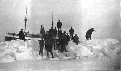 With their ship in background, the men pose onnearby mounds of snow and ice
