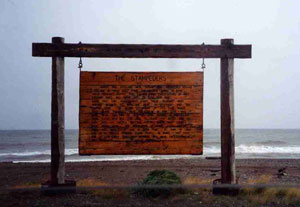 From a photo taken by Patricia Stephenson 1995, on the Nome beach. This wooden marker commemorates The Stampeders.
