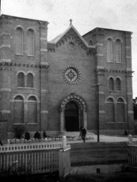 "St. Augustine Cathedral on South Stone Avenue, c. 1903. This was the principal church of the Catholic Diocese at that time and of tremendous importance to the nearby barrios located to the south and west. According to the 1961 guide ""Buildings of Architectural Significance in Tucson,"" St. Augustine's Cathedral's was a ""colonial type of construction, utilizing heavy masonry walls of local burnt brick, originally with cinder footing and Ashlar stone foundation. Original tower terminated 40 feet above ground. In 1929 the building was raised another 40 feet, after underpinning, removing cinder bottom, and replacing with reinforced concrete footing. This was accomplished in four-foot sections. Superstructure was continued in brick with concrete slabs and dome. Plastered on outside and made to conform with Mission arachitecture of the Southwest. Cathedral glass imported from Munich, Germany."