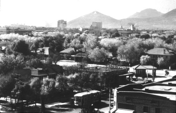 "A 1929 photograph by Professor R. B. Streets from the window of the University library building. In the foreground is the University Drug Store, the trolley and the Pi Phi Sorority House on the southwest corner of Park Avenue and University Boulevard. The Varsity Inn sits west of the sorority house with the Marshall's Texaco Station one lot farther west. The large buildings in the background (from left to right) were Tucson High School at the left edge and above it the Santa Rita Hotel. The Valley National Bank and Pioneer Hotel stand as Tucson's ""twin towers,"" the latter showing directly beneath the ""A"" on the volcanic mountain formerly know as ""Sentinel Peak."" The dome of the Pima County Court House is next in line, followed by the square tower of the Eagle Flour Milling Company."